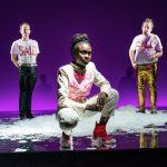 Drei Personen auf einer Bühne mit Badeschaum und violettem Hintergrund, v.l. Patrick Güldenberg, Lorna Ishema, Sascha Nathan