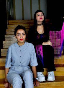 Zwei junge Frauen, sitzen auf einer Treppe.