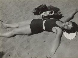 Schwarz-weiß Fotografie einer Frau, die auf dem Rücken im Sand liegt