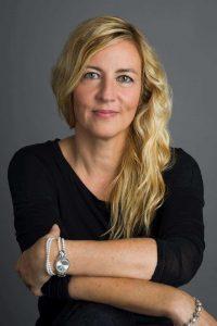 Fotografie von Barbara Miller. Die Frau ist im Profil abgebildet, sie lächelt in die Kamera.