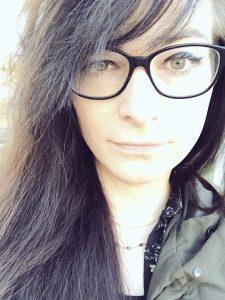 Eine Fraue mit langen, schwarzen Haaren und einer Brille. Nahaufnahme. Sie blickt direkt in die Kamera.