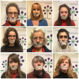 Neun Frauen haben den Mund zugeklebt mit Krepband, auf dem Band steht 219a