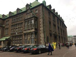 Vor einem Gebäude aus der Gotik stehen mehrere Mercedes. Vor dem Eingang befindet sich eine Greenpeace-Gruppe mit einem Banner.