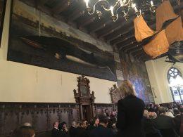 In einem Saal hängt ein großes Gemälde auf dem ein Wal abgebildet ist. Von der Decke hängt ein Kronleuchter und ein altes Kriegsschiff