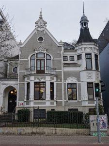 Auf dem Foto ist ein alt-bremer Haus zu sehen, welches über einen Turm verfügt. Davor ist eine Ampel zu sehen, die auf grün steht