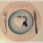 Auf dem Foto ist ein angebissener Berliner in Herzform zu sehen, dessen Marmeladeninhalt ausläuft