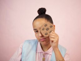 Fotografie der Sängerin Fatima. Sie trägt ein rosanes Oberteil mit Knopfleiste und einer hellblauen Weste. In der linken Hand hält sie einen großen Chocolate-Chip-Cookie, mit dem ihr linkes Auge verdeckt.