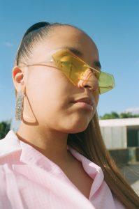 Fotografie der Sängerin Fatima im Halbprofil. Sie trägt eine halbtransparente gelbe Sonnenbrille und lange glitzernde Ohrringe und ein rosanes Oberteil.