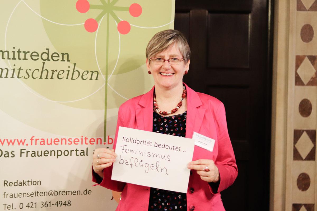 """Maren Bock hält einen Zettel, auf dem steht """"Solidarität bedeutet... Feminismus beflügeln"""""""
