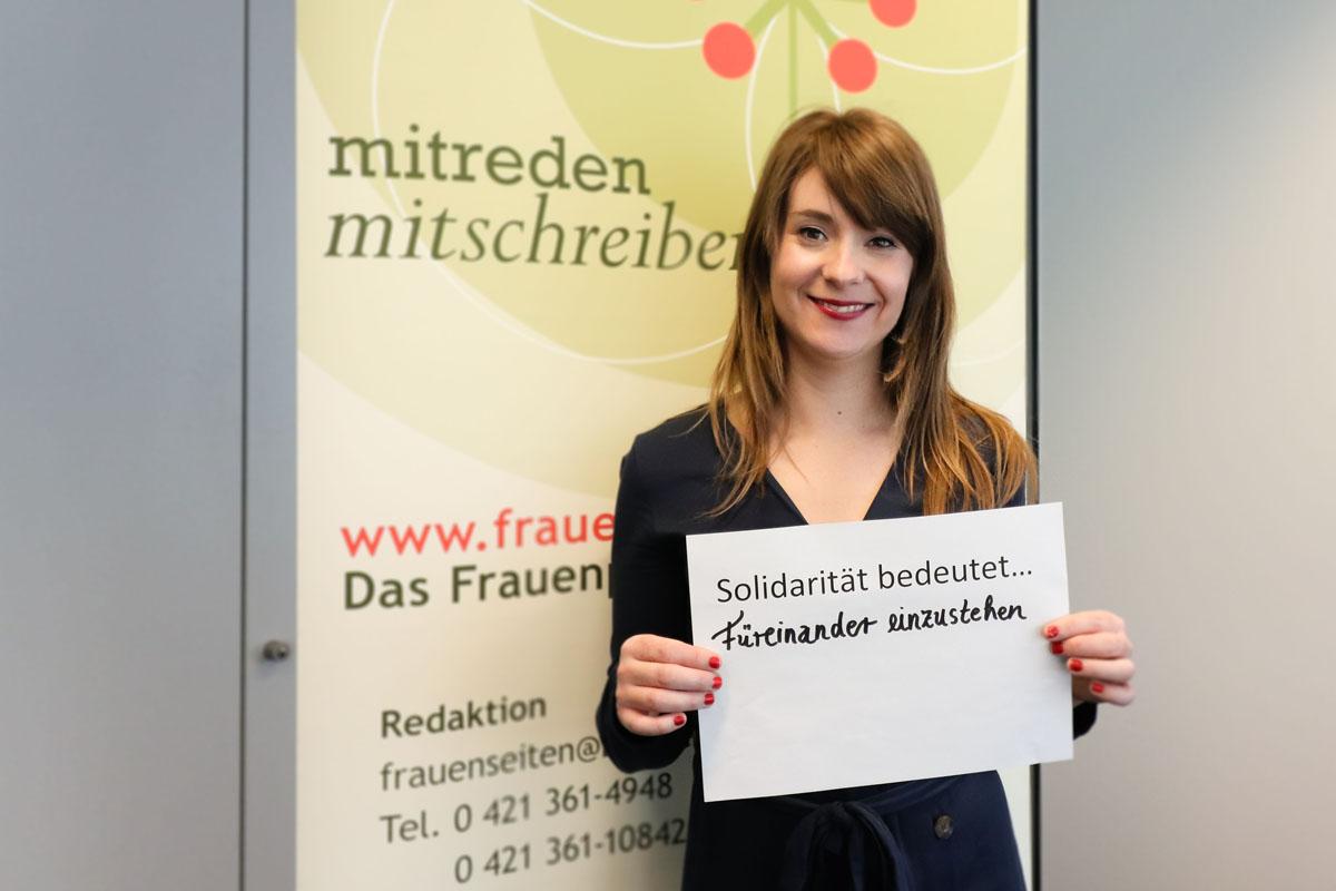 """Eine Frau hält ein Bild, auf dem steht """"Solidarität bedeutet... füreinander einzustehen"""""""