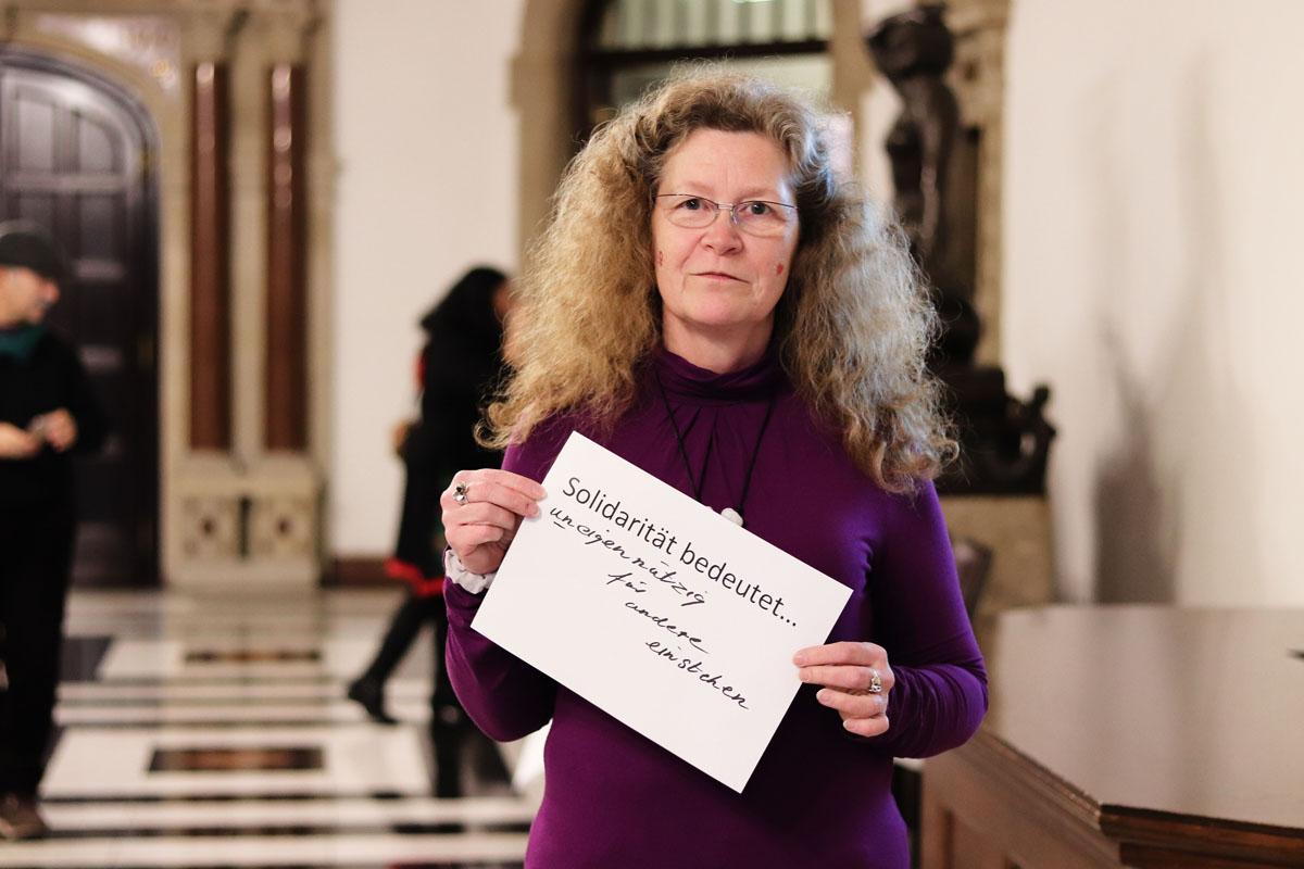 """Eine Frau hält ein Bild, auf dem steht """"Solidarität bedeutet... uneigennützig für andere einstehen"""""""
