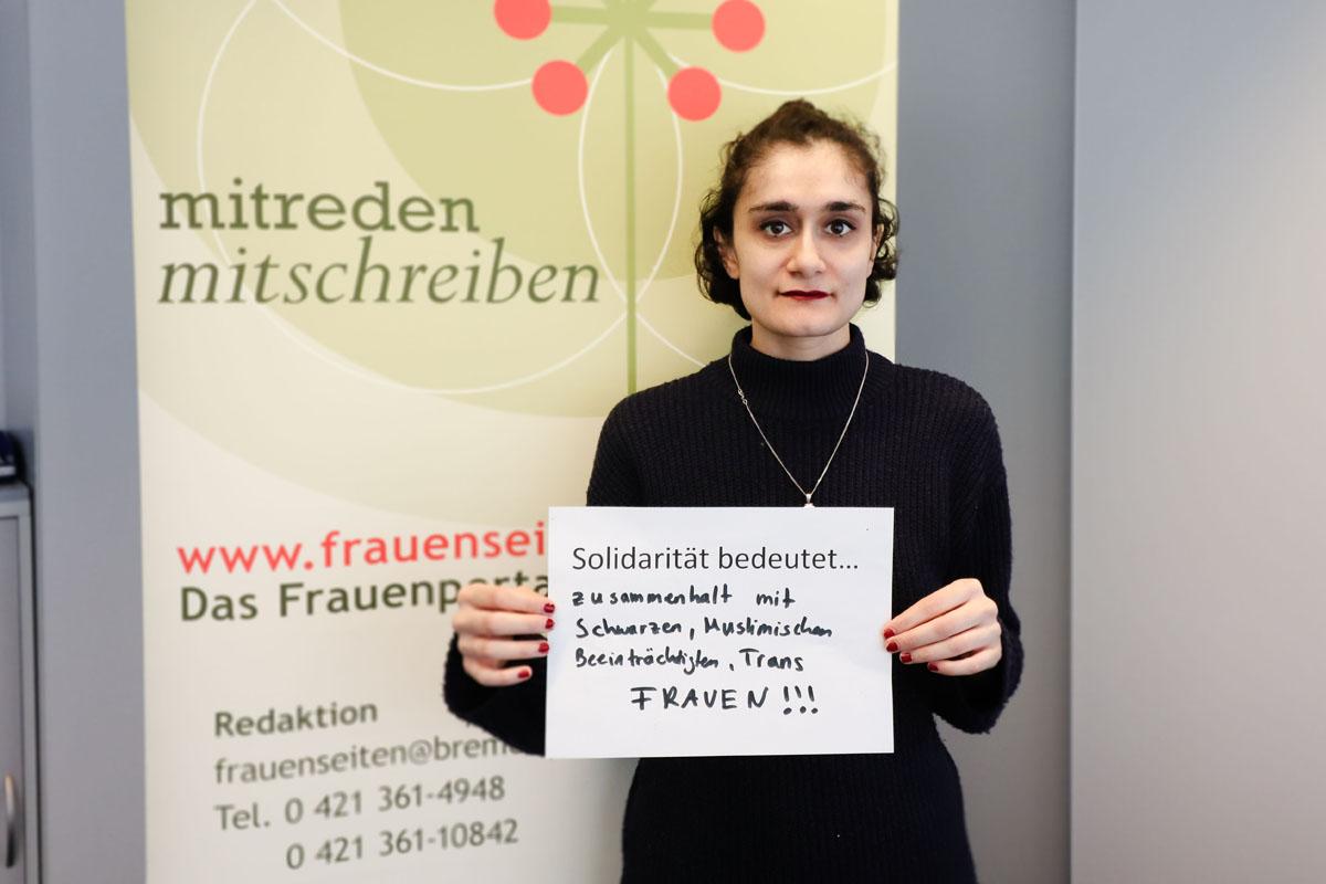 """Eine Frau hält ein Bild, auf dem steht """"Solidarität bedeutet... Zusammenhalt mit Schwarzen, Muslimischen, Beeinträchtigten, Trans FRAUEN!!!"""""""