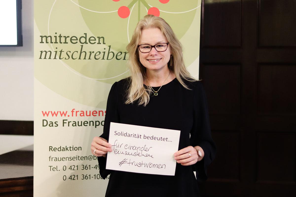 """Frau Kappert-Gonther hält einen Zettel, auf dem steht """"Solidarität bedeutet...füreinander einzustehen #trustwomen"""""""
