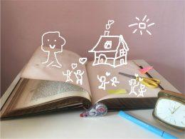 Auf dem Bild ist ein aufgeschlagenes, vergilbtes Buch zu sehen. Auf der aufgeschlagenen Seite sieht man ein gezeichnetes Luftschloss mit lächelndem Baum, Sonne und Menschen, die jubelnd ihre Hände in die Höhe werfen