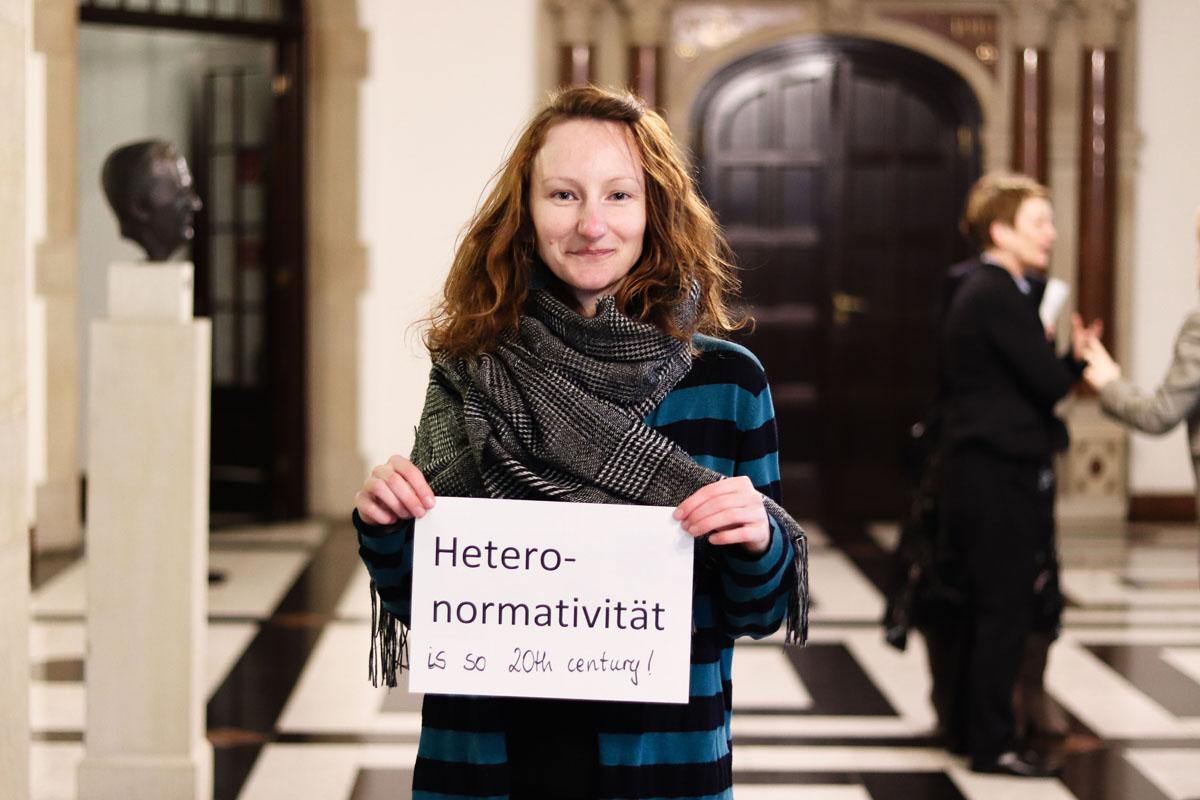 """Eine Frau hält ein Bild, auf dem steht """"Heteronormativität ist so 20th century!"""""""