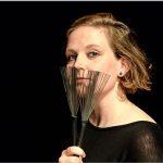 Das Bild zeigt eine Frau, die Schlagzeugpinsel vor ihr Gesicht hält.