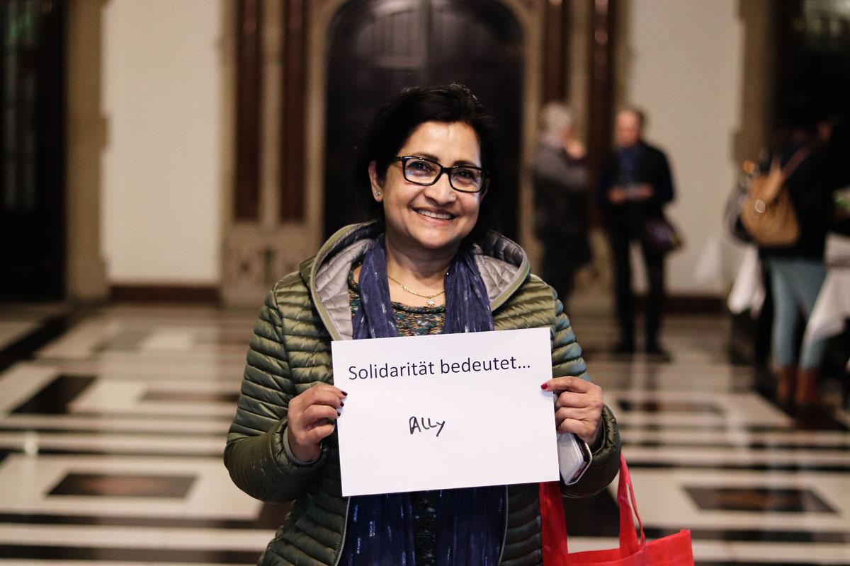 """Eine Frau hält ein Bild, auf dem steht """"Solidarität bedeutet... Ally"""""""