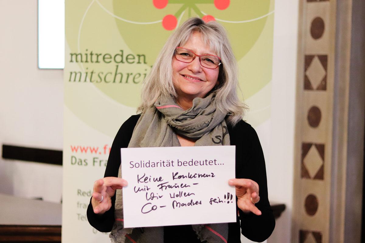 """Eine Frau hält ein Bild, auf dem steht """"Solidarität bedeutet...keine Konkurrenz mit Frauen - Wir wollen Co-Madres sein!!"""""""