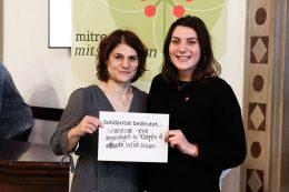 """Das Bild zeigt zwei Frauen, die einen Zettel vor sich halten. Auf dem Zettel seht """"Solidarität bedeutet... gemeinsam gegen ungerechtigkeit zu kämpfen & niemanden zurück zu lassen"""""""