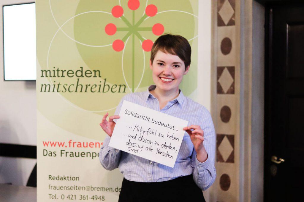 """Eine Frau hält ein Bild, auf dem steht """"Solidarität bedeutet...Mitgefühl zu haben und daran zu denken, dass wir alle Menschen sind!"""