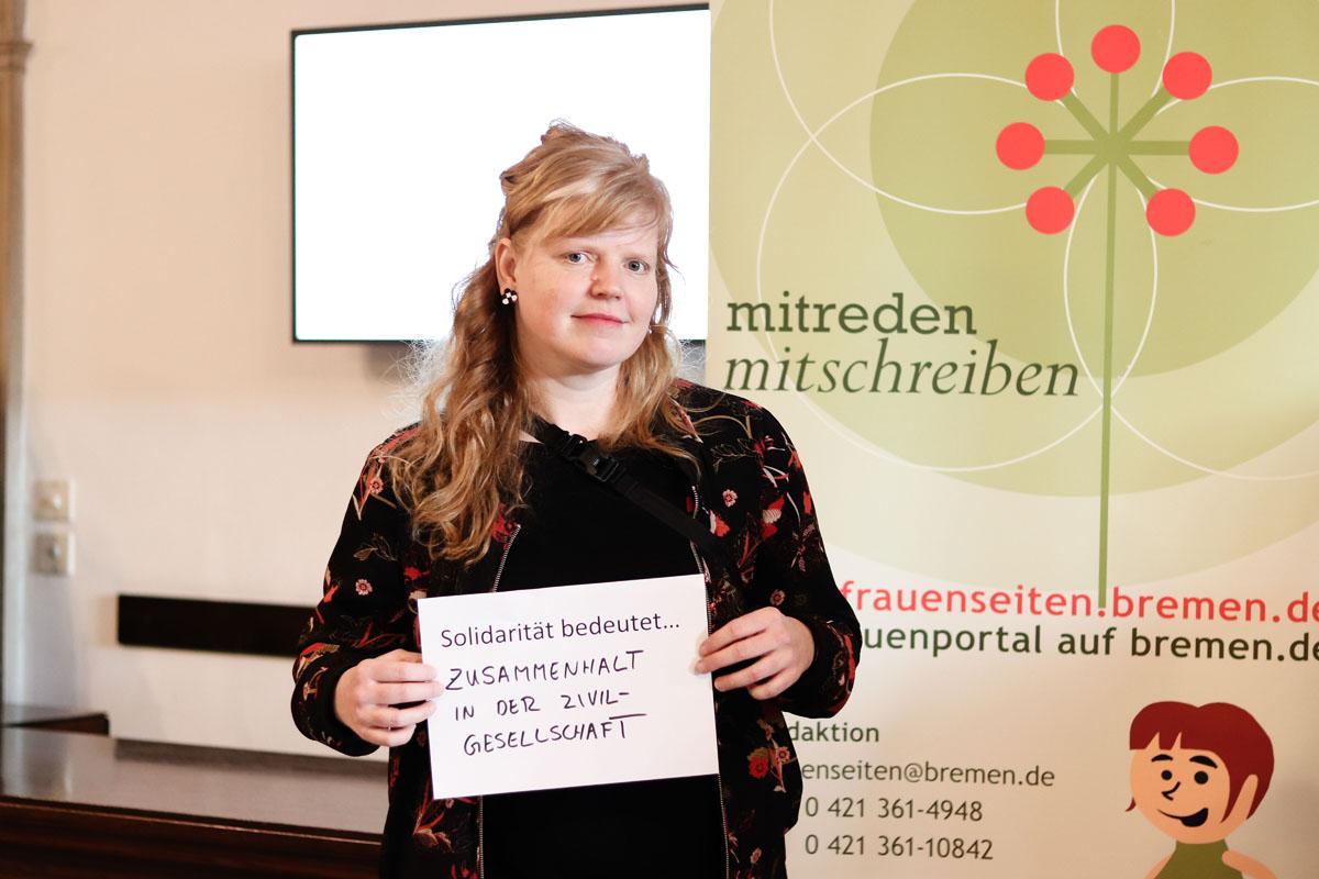 """Eine Frau hält ein Bild, auf dem steht """"Solidarität bedeutet... Zusammenhalt in der Zivilgesellschaft"""""""