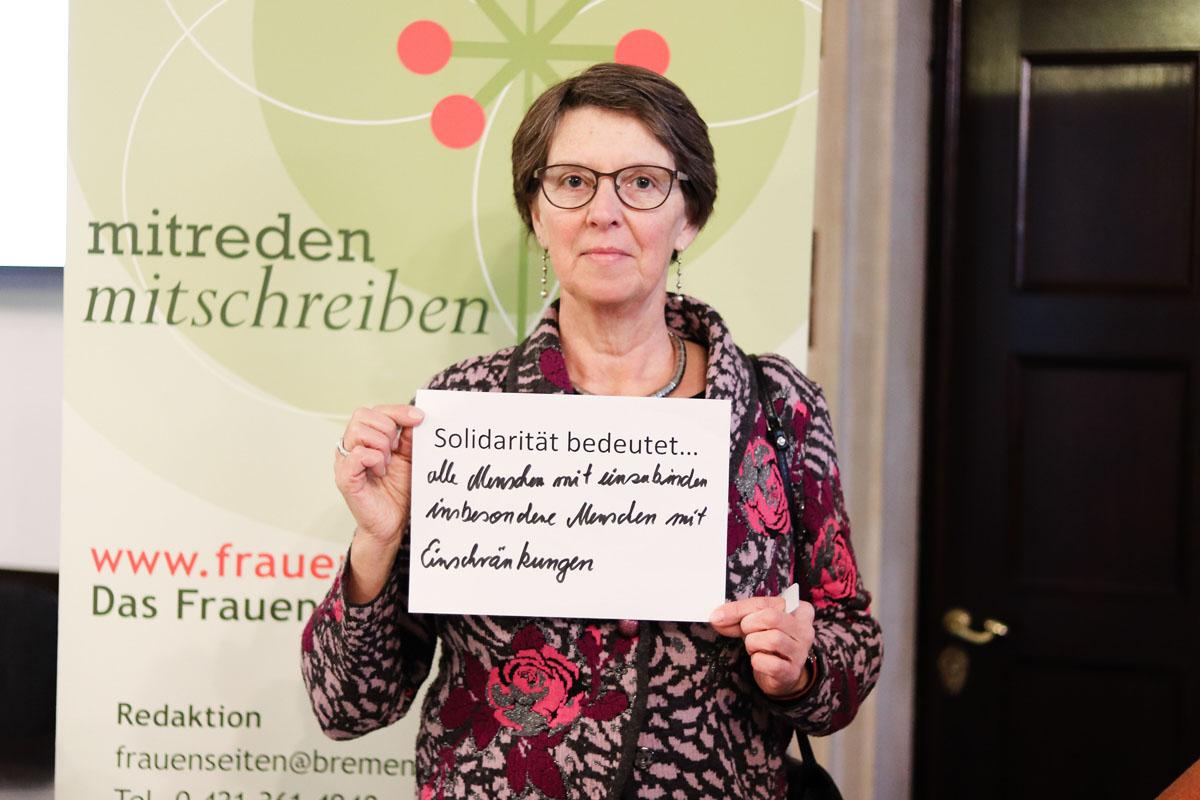 """Eine Frau hält ein Bild, auf dem steht """"Solidarität bedeutet... alle Menschen mit einzubinden insbesondere Menschen mit Einschränkungen"""""""