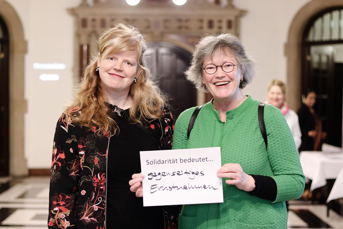 """Ulrike Hauffe und Renate Strümpel mit einem Zettel, auf dem steht """"Solidarität bedeutet..gegenseitiges Ernstnehmen"""""""