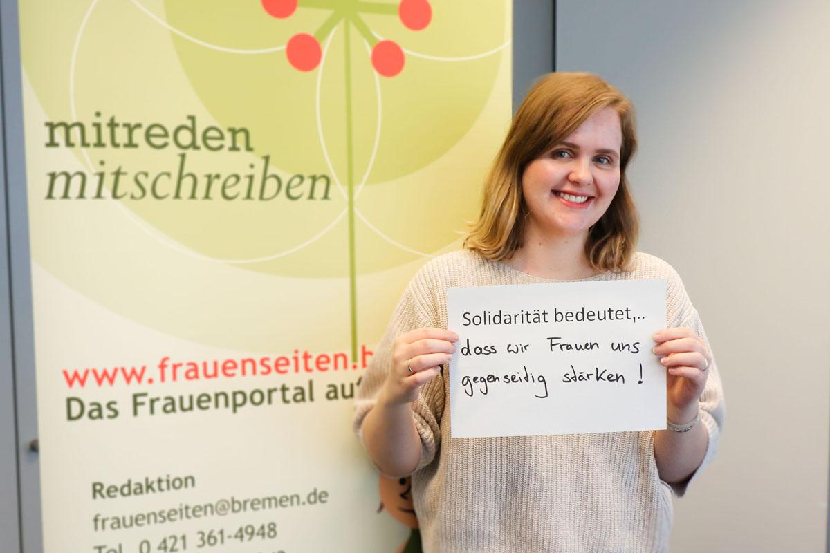 """Eine Frau hält ein Bild, auf dem steht """"Solidarität bedeutet... dass wir Frauen uns gegenseitig stärken"""""""