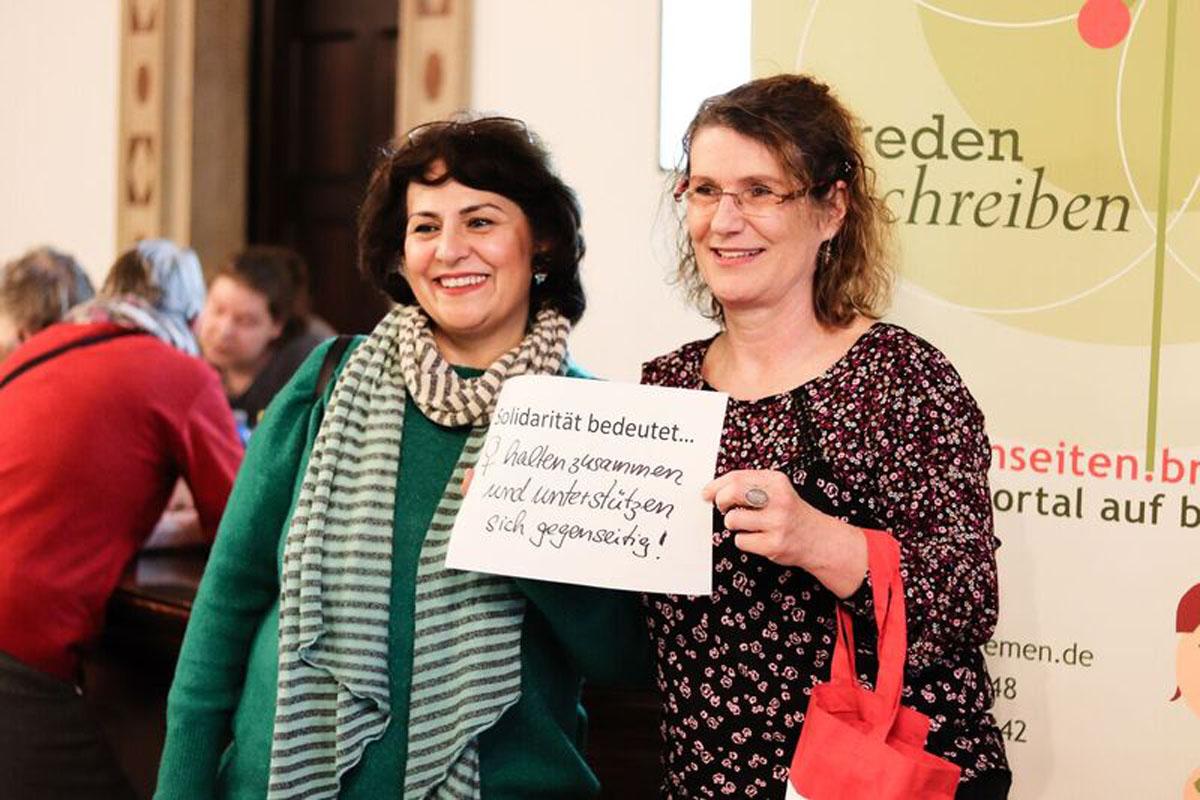 """Zwei Frauen halten ein Bild, auf dem steht: """"Solidarität bedeutet...Frauen halten zusammen und unterstützen sich gegenseitig'"""""""