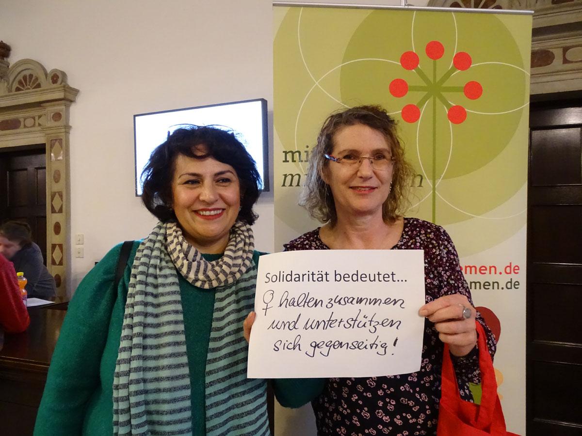 """Das Bild zeigt zwei Frauen, die einen Zettel vor sich halten, auf dem steht: """"Solidarität bedeutet Frauen halten zusammen und unterstützen sich gegenseitig""""."""