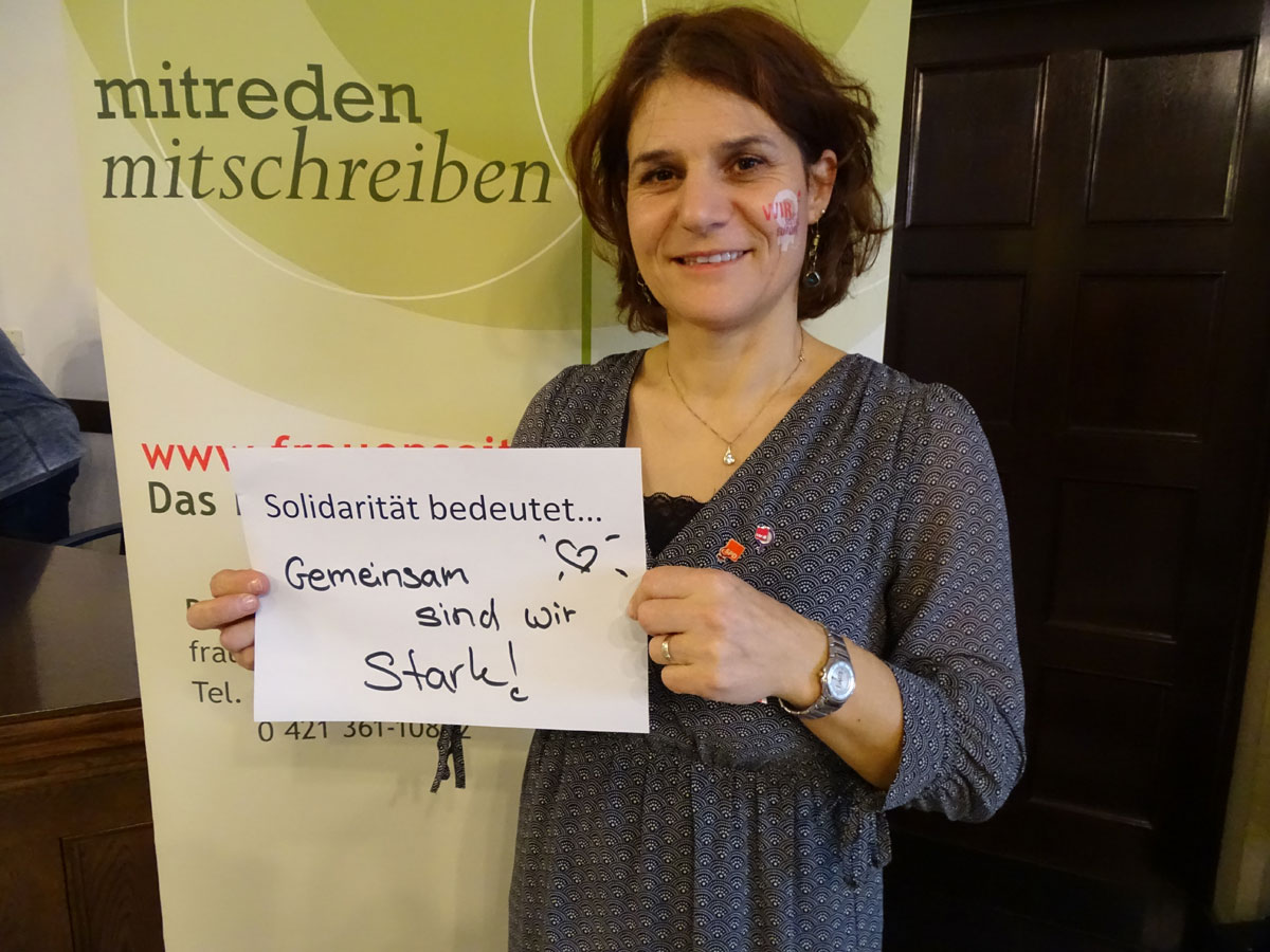 """Das Bild zeigt zwei junge Frauen, die jeweils einen Zettel vor sich hält, auf dem steht: """"Solidarität bedeutet Gemeinsam sind wir stark""""."""