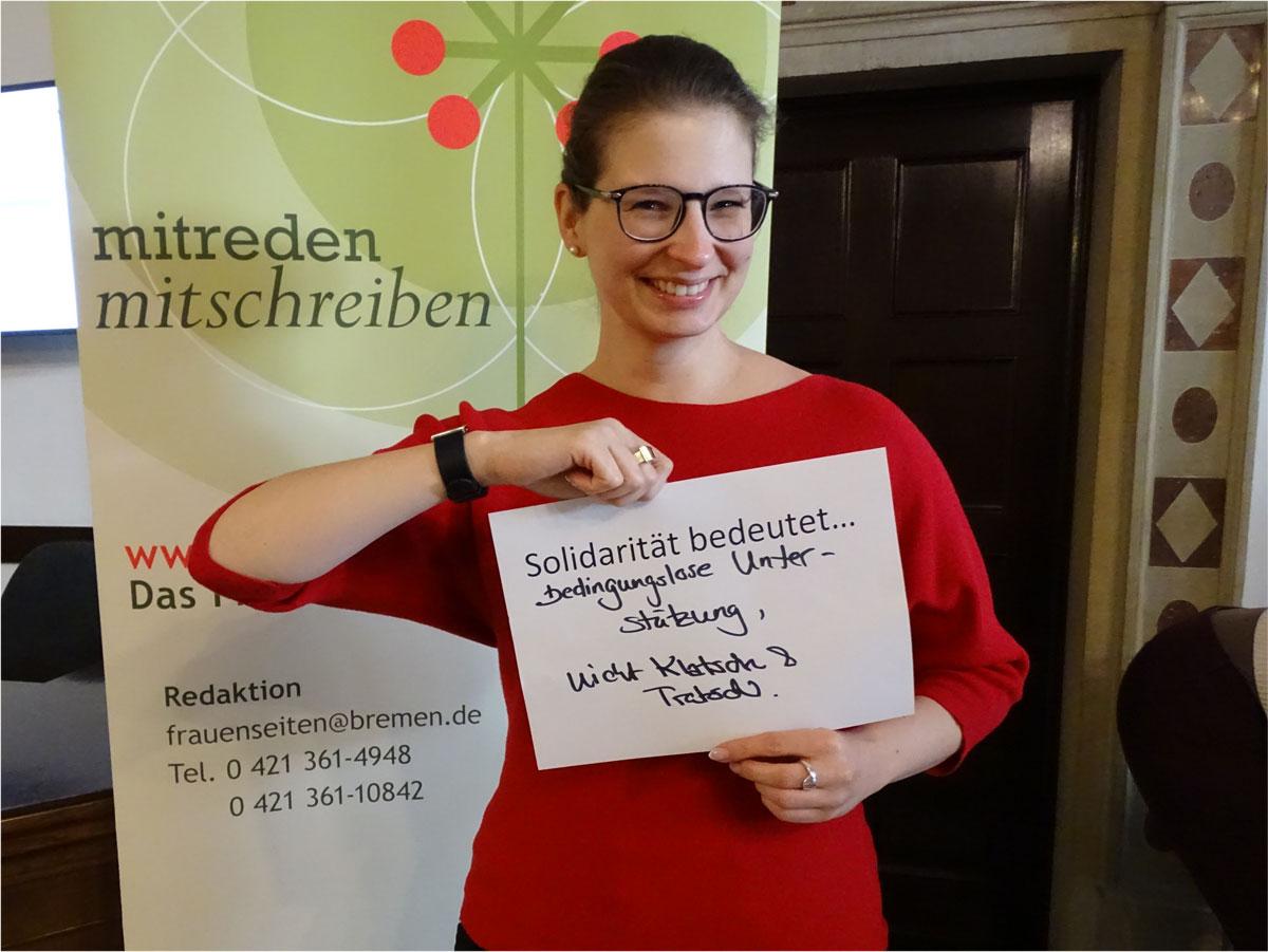 """Das Bild zeigt eine Frau, die einen Zettel vor sich hält, auf dem steht: """"Solidarität bedeutet bedingungslose Unterstützung, nicht Klatsch und Tratsch""""."""