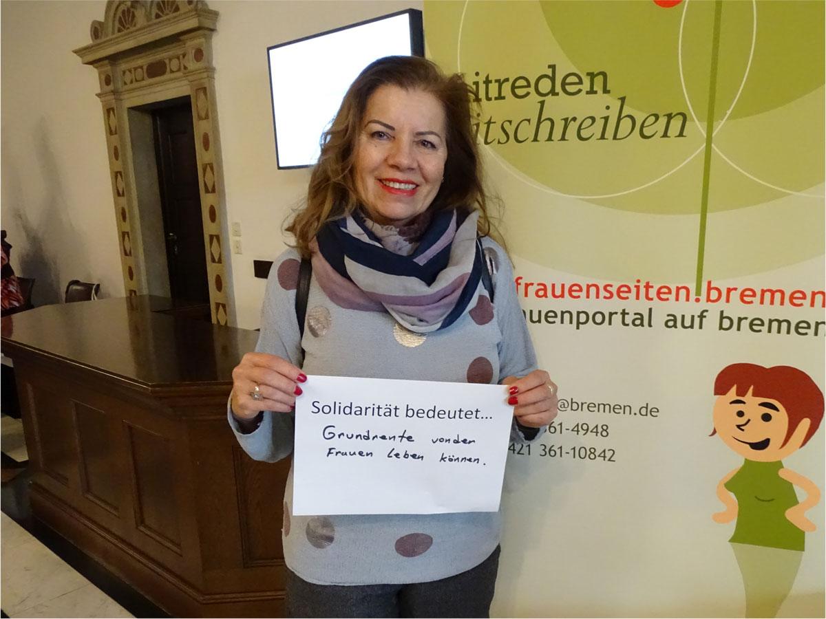 """Das Bild zeigt eine Frau, die einen Zettel vor sich hält, auf dem steht: """"Solidarität bedeutet Grundrente, von der Frauen leben können""""."""