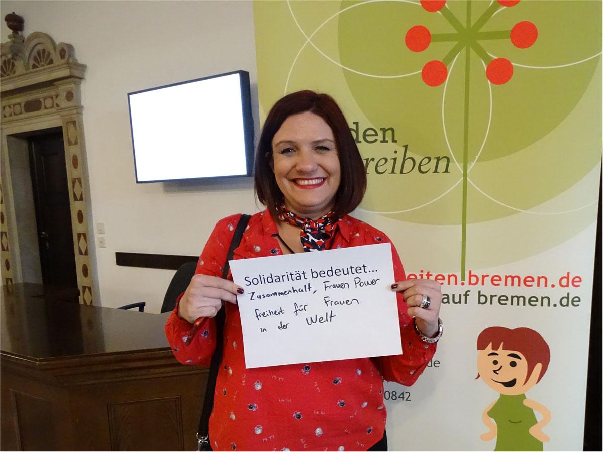 """Das Bild zeigt eine Frau, die einen Zettel vor sich hält, auf dem steht: """"Solidarität bedeutet Zusammenhalt, Frauenpower, Freiheit für Frauen in der Welt""""."""