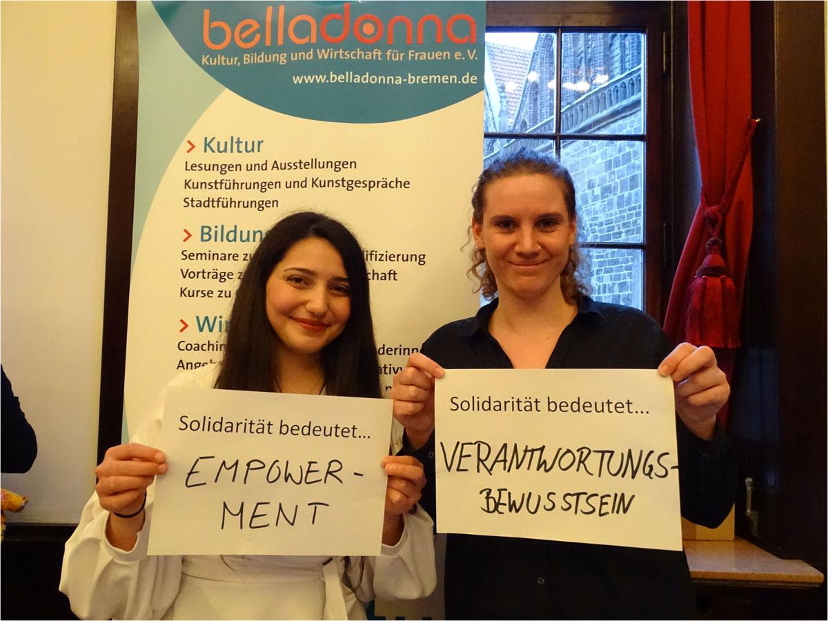 """Das Bild zeigt zwei junge Frauen, die jeweils einen Zettel vor sich halten. Auf dem einen steht: """"Solidarität bedeutet Empowerment"""", auf dem anderen """"Solidarität bedeutet Verantwortungsbewusstsein""""."""