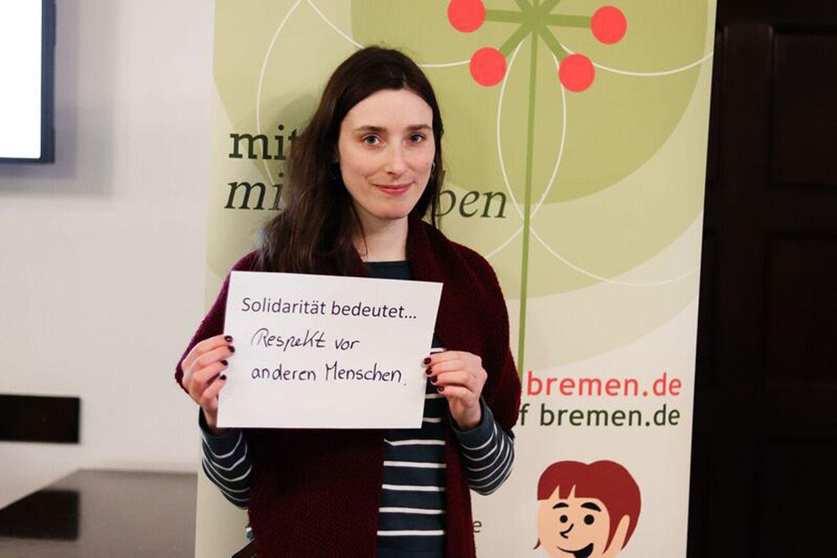 """Eine Frau hält ein Bild, auf dem steht """"Solidarität bedeutet... Respekt vor anderen Menschen"""""""