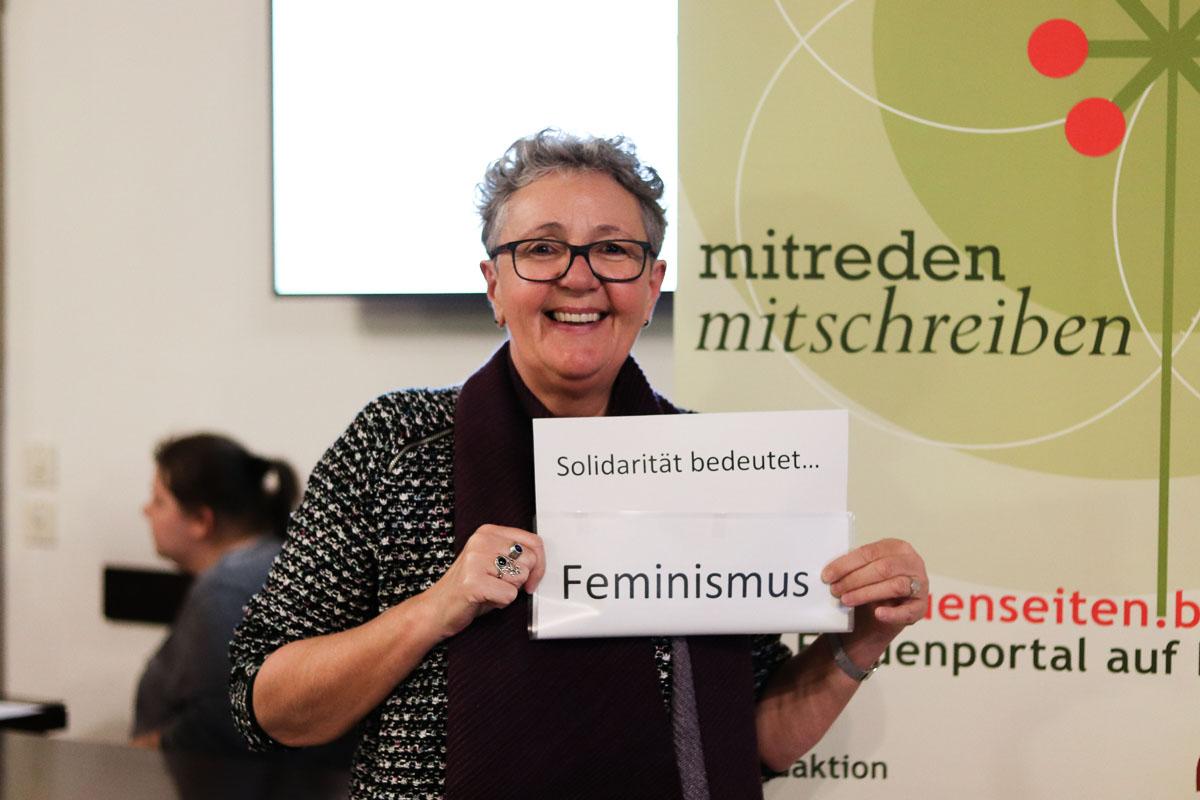 """Eine Frau hält ein Bild, auf dem steht """"Solidarität bedeutet... Feminismus"""""""