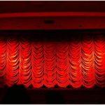Es ist ein roter Vorhang in einem Kinosaal von vorne zu sehen