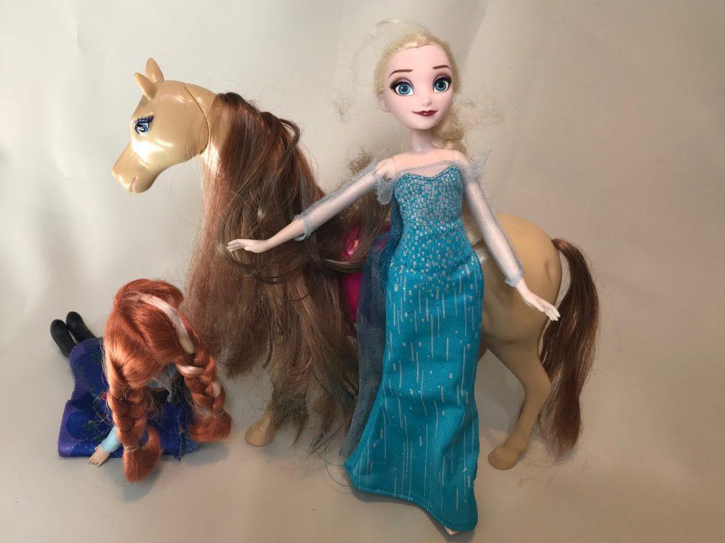 Barbie Elsa steht vor Barbie Pferd, rechts neben dem Pferd sitzt eine weitere Babie