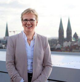 Die Senatorin steht lächelnd vor der Bremer Skyline
