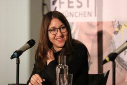 Foto von Deborah Feldman, die auf einer Bühne vor einem Mikrofon sitzt und lacht