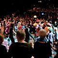 Eine Gruppe tanzender Frauen im Hintergrund ein Orchester