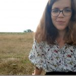 Eine Frau, Luise, im Vordergrund mit Bluse, braunen Haaren und Brille. Im Hintergrund eine Wiese
