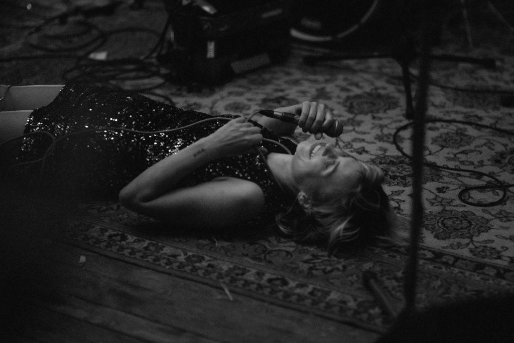 Frau liegt mit Mikrophon auf der Bühne