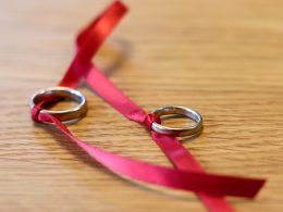 Zwei Eheringe sind mit einem roten Band verknotet.