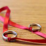 Zwei Eheringe sind mit einem roten Stoffband verknotet.