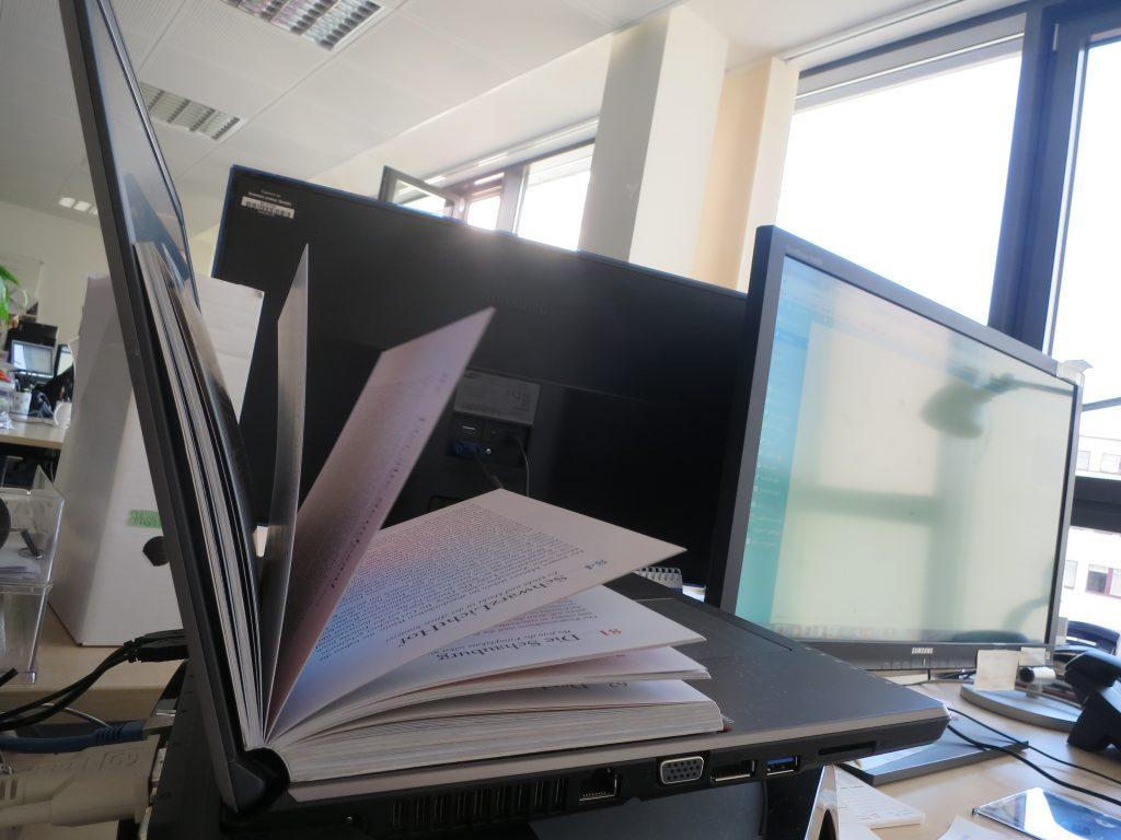 Informatica Feminale, Laptop mit inliegendem Buch und Bildschirm im Hintergrund