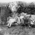 Schwarz-Weiß Bild von einer Frau, einem Mann und einem Kind, die auf Liegestühlen in einem Garten liegen. Der Mann liest eine Zeitung.
