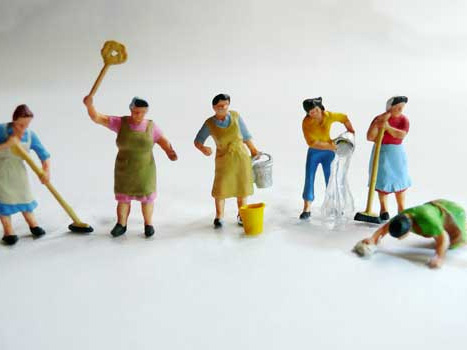 6 Miniatur-Hausfrauen putzen nebeneinander