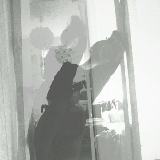 Schwarz-weiß Fotografie einer Frau von hinten, die sich in Schieflage gegen einen Türrahmen lehnt.